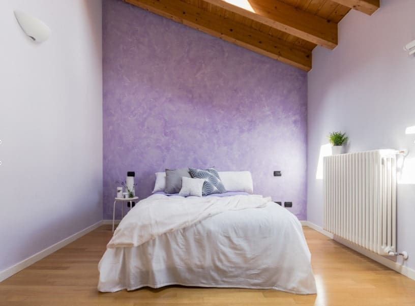 Primary bedroom featuring a white bed surrounded by white and purple walls along with a wooden ceiling with exposed beams and a skylight.