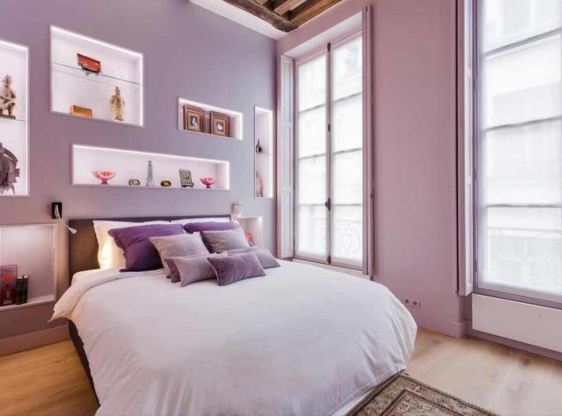 A focused shot at this primary bedroom's cozy bed setup surrounded by purple walls and a tall ceiling with beams. The wall features multiple wall decors that look attractive.