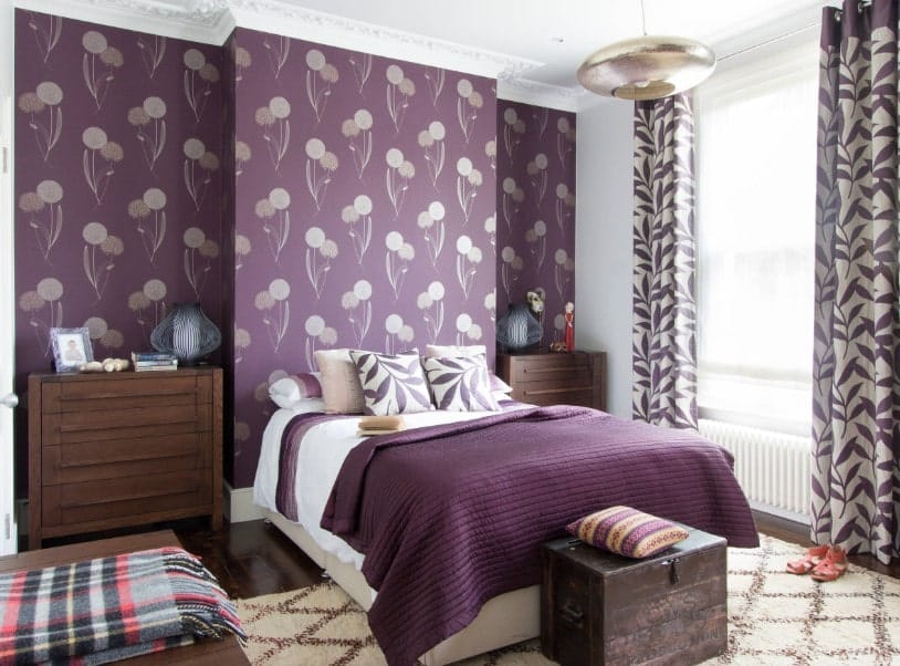 Primary bedroom boasting a stylish purple wall and a classy white ceiling. The room offers a comfy bed with bedside tables on both sides.