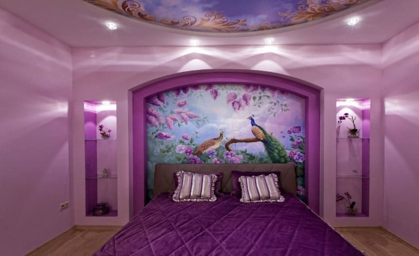 A primary bedroom with a stunning decorated wall and ceiling, along with a purple bed with built-in shelving on both sides.