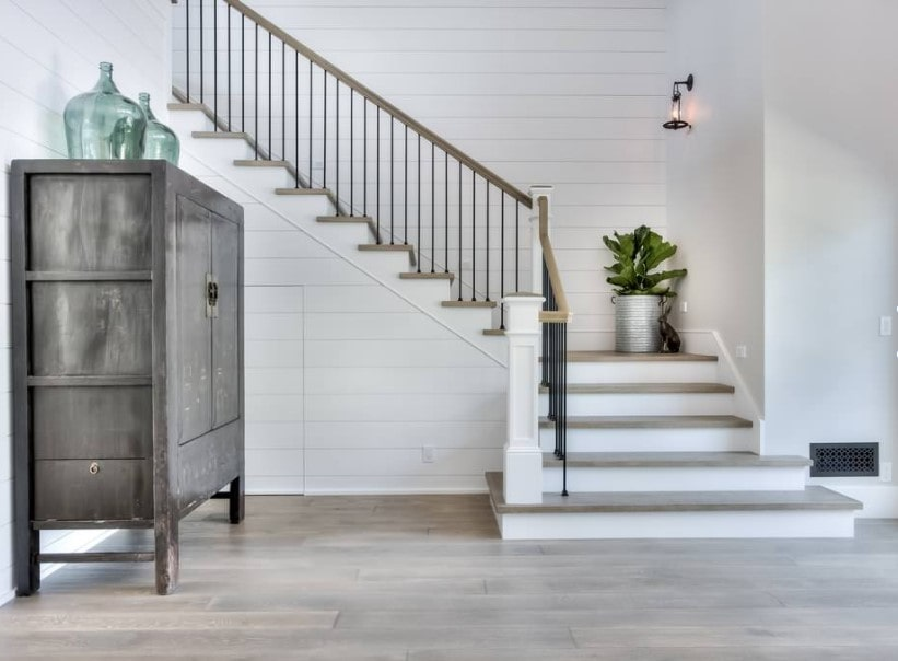 This home's foyer features a quarter-turn staircase featuring iron railings and hardwood steps, lighted by wall lights set on the white walls.