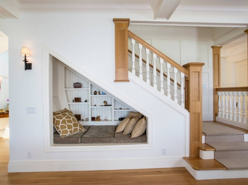 A gorgeous staircase with a built-in bed setup underneath. The stairs feature hardwood steps along with hardwood handrails.