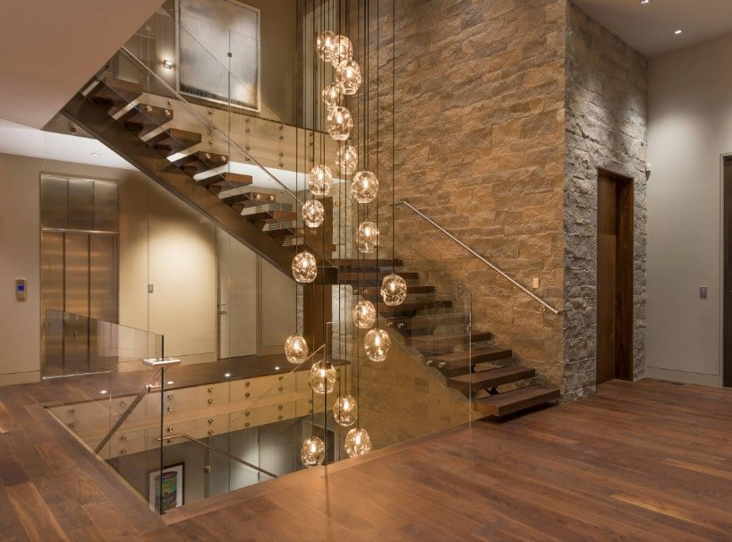 This home boasts a staircase lighted by jaw-dropping ceiling lights hanging from the high ceiling. The home features hardwood flooring and glass railings.
