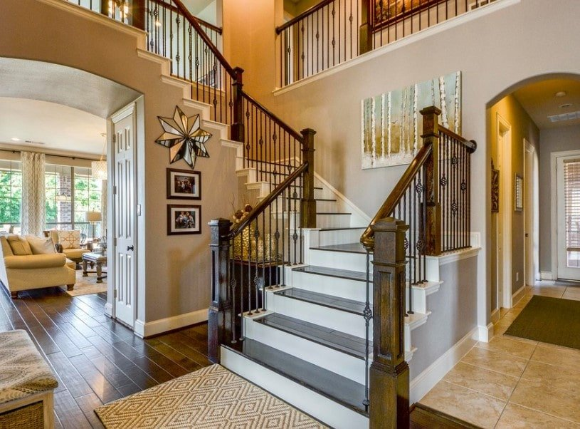 This home features hardwood floors, gray walls and a high ceiling, together with the staircase featuring hardwood steps.