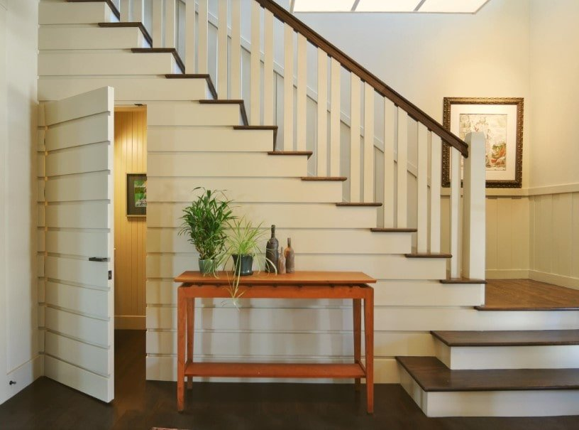 This home boasts a quarter-turn staircase featuring hardwood steps and white railings. There's a doorway underneath the staircase too.