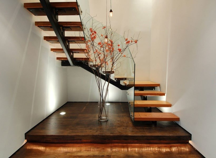 A focused look at this home's stunning staircase with hardwood steps and glass railings, surrounded by white walls.