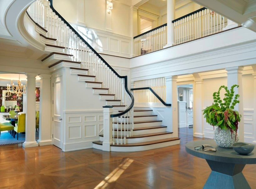 A grand foyer boasting stylish hardwood floors and a two-storey ceiling. There's a gorgeous staircase leading to the home's second floor.