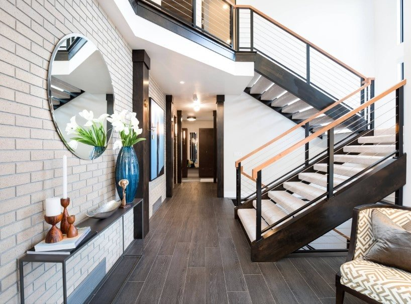 This home features hardwood floors and a brick wall. It also offers a gorgeous staircase with white steps and wooden handrails.