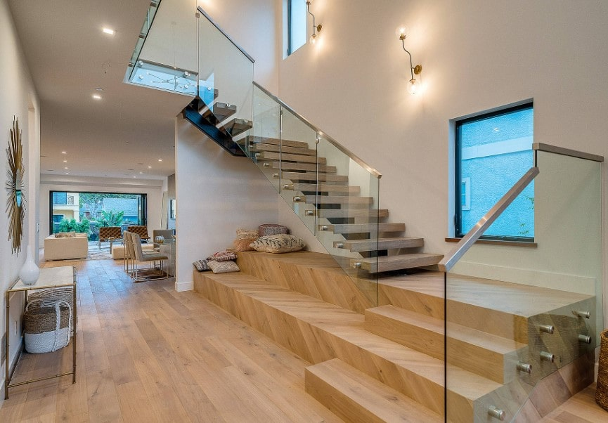 This home boasts a modern quarter-turn staircase that looks very stylish. It has glass railings and is lighted by magnificent wall lights.