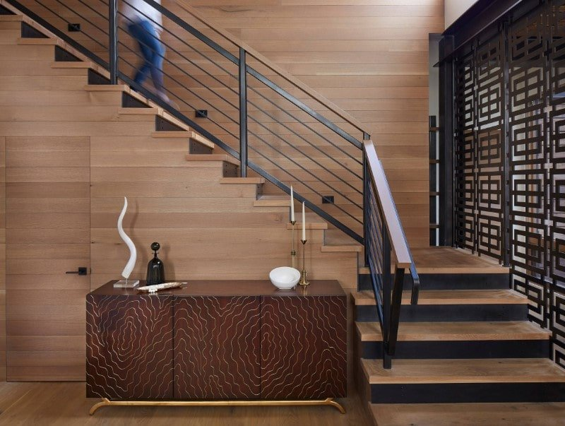 A focused look at this rustic modern home's quarter-turn staircase with iron railings. It also has an elegant side table on the side.