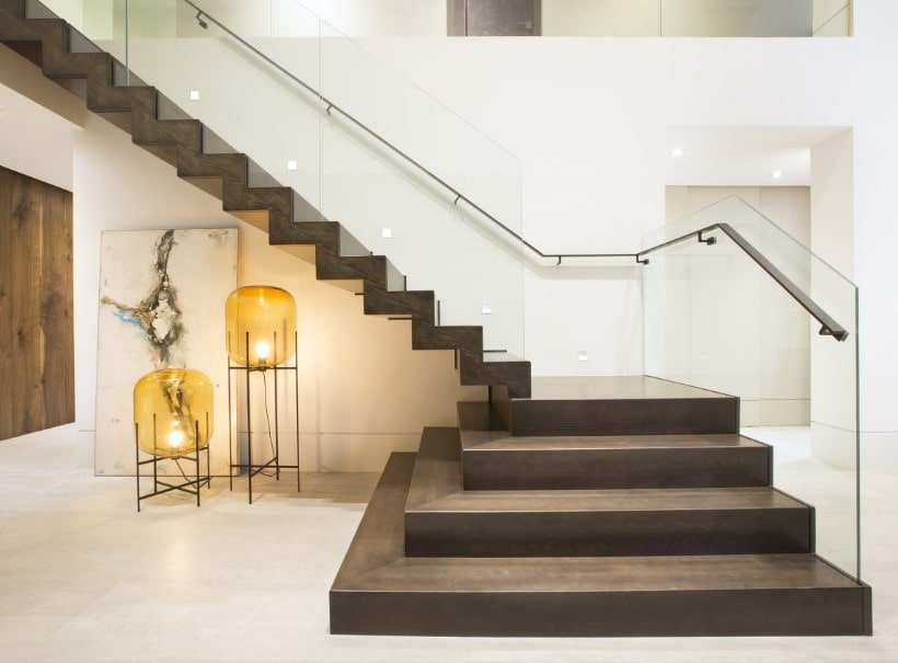 A close up look at this modern home's modish quarter-turn staircase boasting hardwood steps and glass railings, surrounded by the home's white walls.