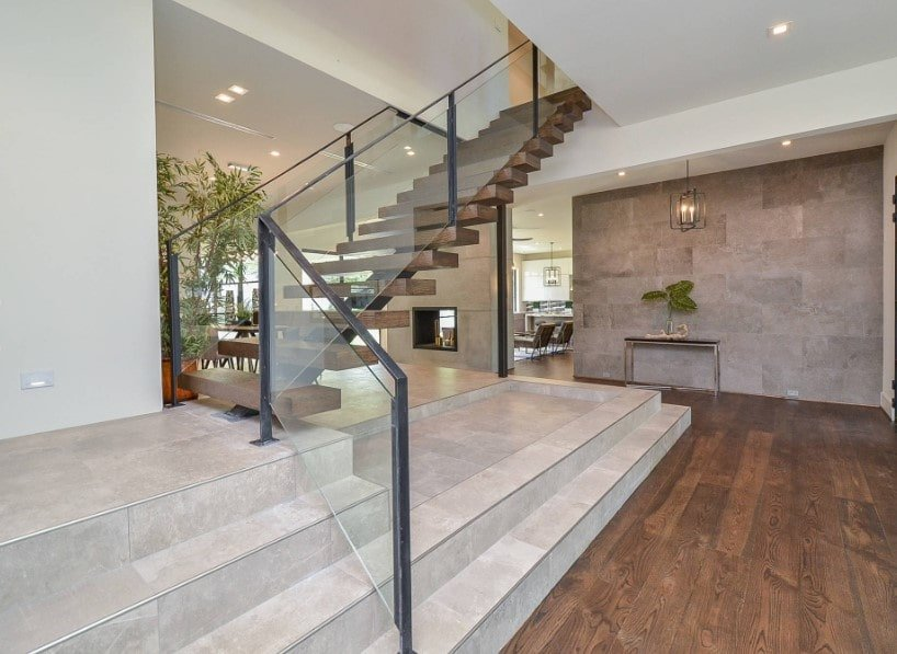 A focused look at this home's modern staircase with hardwood steps and glass railings. The home features hardwood floors and stylish walls.