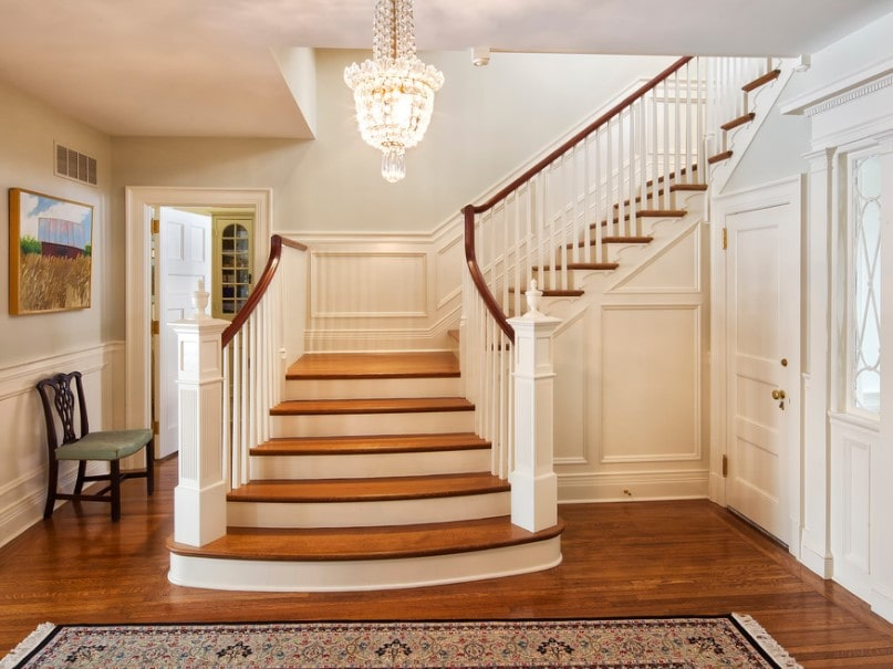 A focused shot at this foyer's half-turn staircase featuring hardwood steps and white railings. The staircase is lighted by a breathtaking chandelier.