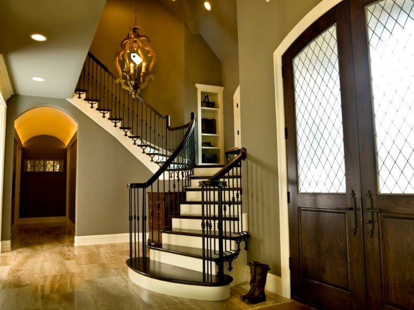 This home's foyer features a quarter-turn staircase featuring classy dark hardwood steps and handrails. The area is lighted by a glamorous ceiling light as well.