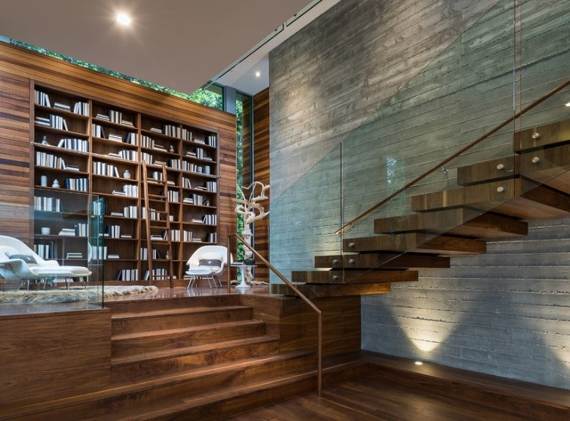 A stunning living space featuring a hardwood platform connected to the half-turn staircase with hardwood steps and glass railings. The area also offers large bookshelves as well.