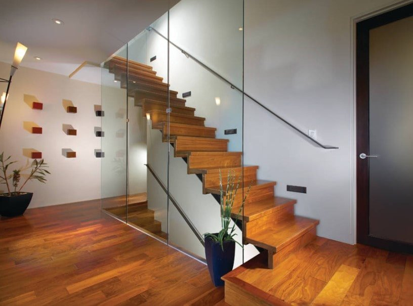 A modern home featuring a staircase boasting hardwood steps matching the home's hardwood flooring. The staircase also boasts stylish glass railings.