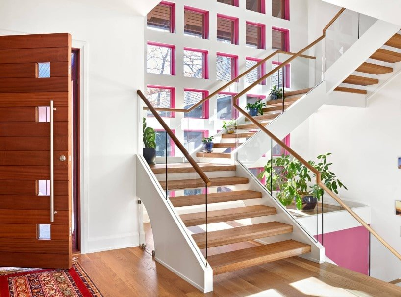 A bright entry featuring white walls and hardwood floors. The home has a quarter-turn staircase featuring hardwood steps and glass railings.