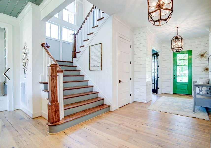 A spacious entry featuring white walls and hardwood floors. The home offers a quarter-turn staircase with hardwood steps and handrails, surrounded by the home's white walls.