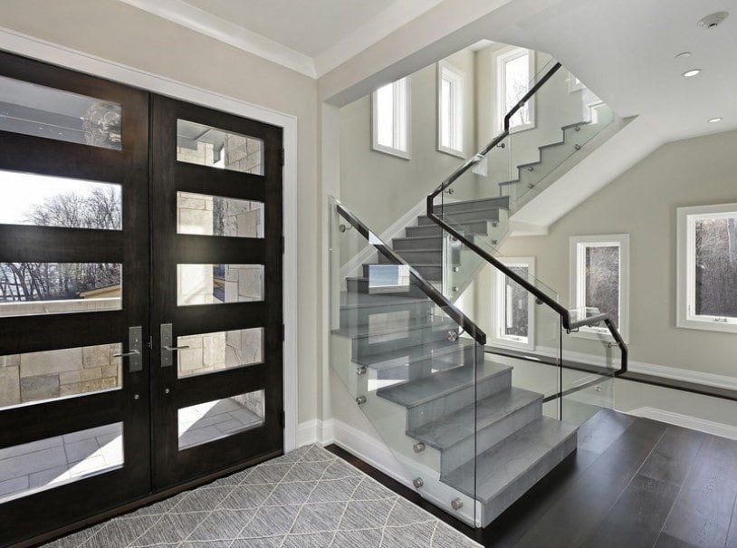 This foyer features dark hardwood floors and light gray walls. There's a quarter-turn staircase featuring carpeted steps and glass railings.