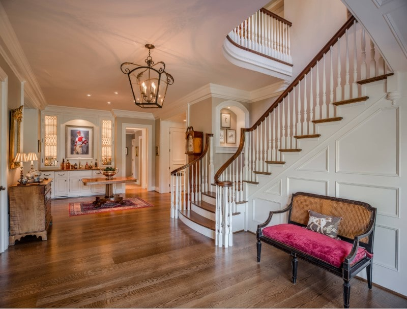 A spacious foyer featuring hardwood flooring and white walls. The area is lighted by a gorgeous ceiling light. There's a staircase leading to the home's second floor as well.