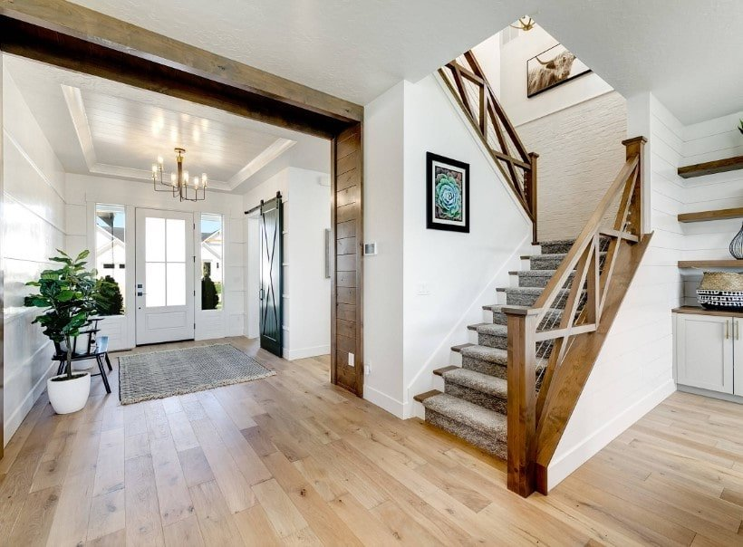 A foyer featuring white walls, hardwood floors and a tray ceiling lighted by a charming chandelier. It also offers a staircase with hardwood steps, handrails and railings.