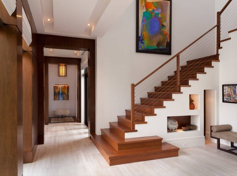 A modern home featuring a gorgeous staircase featuring hardwood steps surrounded by the home's white walls with artistic wall decor.