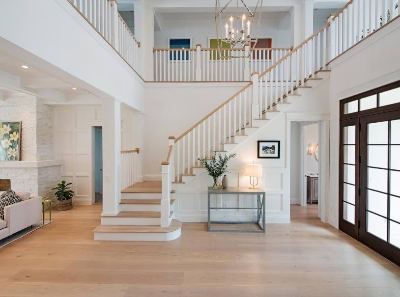 A spacious foyer featuring hardwood flooring and white walls, together with the two-storey ceiling. The area features a quarter-turn staircase lighted by a gorgeous chandelier.