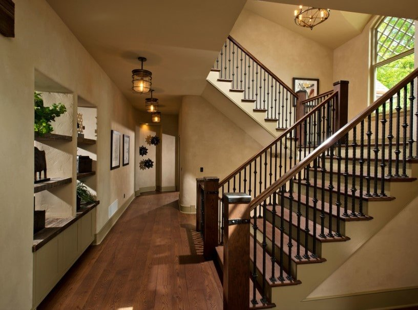 This home's hallway features hardwood floors and classy pendant lights. The area offers a large staircase featuring hardwood steps and iron railings.