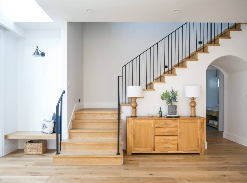 A focused shot at this home entry's quarter-turn staircase featuring hardwood steps and iron rails, surrounded by the home's white walls.