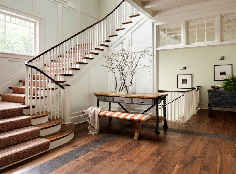 A spacious home landing featuring hardwood floors and a tall ceiling. It also has a gorgeous-looking quarter-turn staircase with hardwood steps covered by brown carpet.