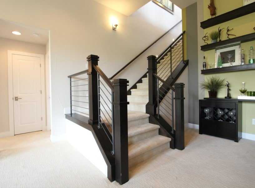 This home's entry boasts carpeted flooring and recessed ceiling lights. It offers a quarter-turn staircase with carpeted steps as well, along with hardwood handrails, lighted by wall lights.