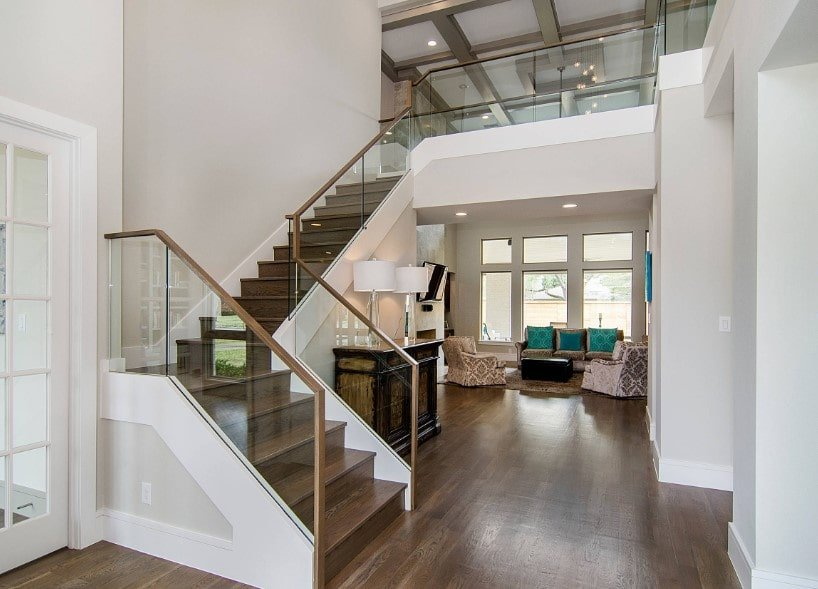 This home's entry features hardwood floors and a two-storey ceiling. It also features a quarter-turn staircase with hardwood steps and handrails, along with glass railings.