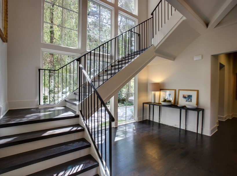 A closer look at the home's quarter-turn staircase with dark hardwood steps. The home features hardwood floors and glass windows.