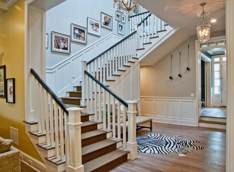 This home's foyer features hardwood floors and light gray walls. It has a quarter-turn staircase with carpeted steps and white railings, lighted by a classy chandelier as well.
