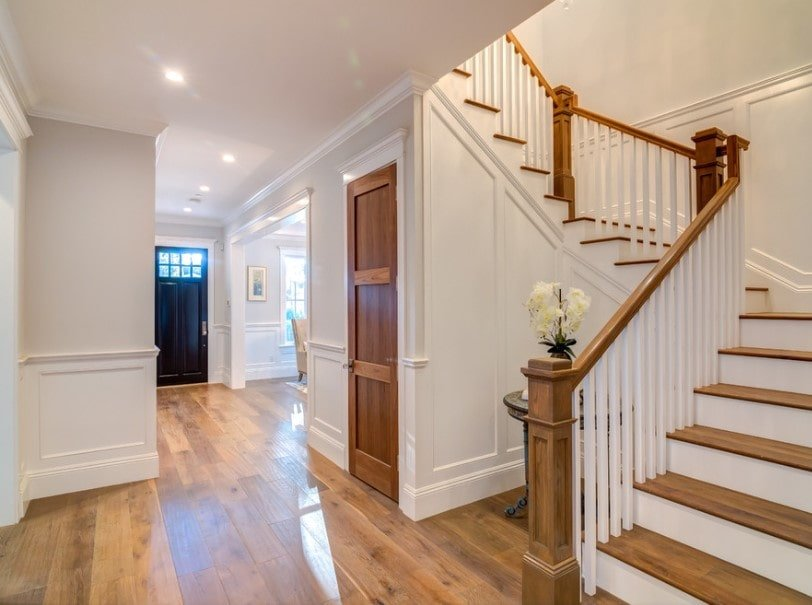 A home with hardwood floors and white walls. It features a quarter-turn staircase featuring hardwood steps and white iron railings.