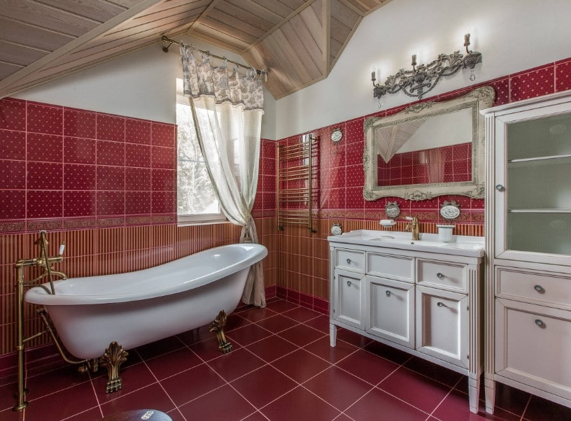 Primary bathroom with decorated red walls and red tiles floors. The room offers a classy freestanding soaking tub along with a sink counter lighted by gorgeous wall lights.