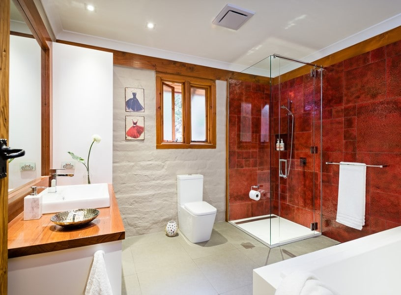 This primary bathroom boasts a walk-in shower and a freestanding soaking tub, along with a sink counter featuring a vessel sink. The room has beautiful red tiles walls.