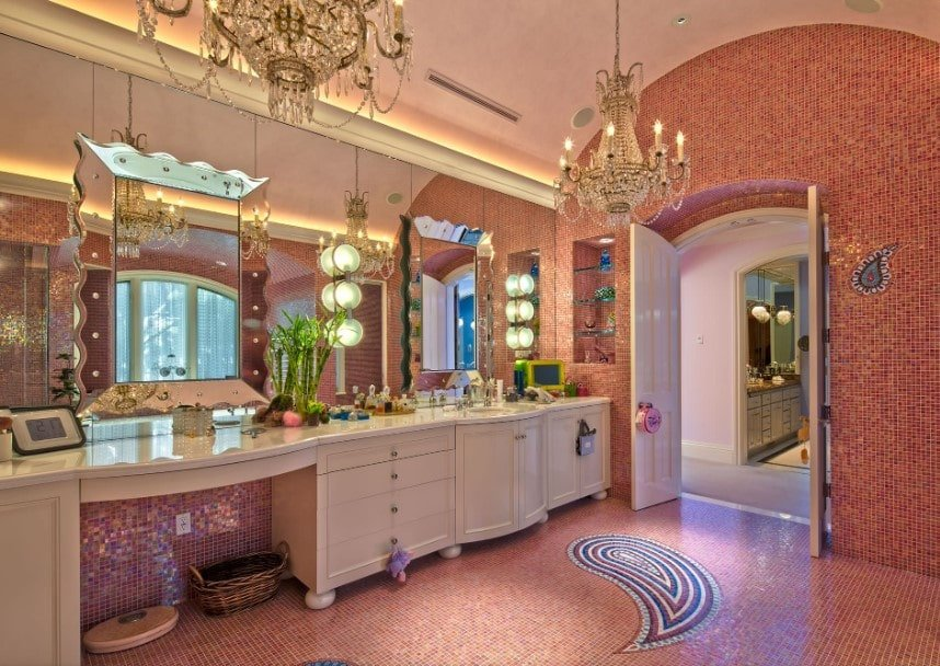 Primary bathroom with gorgeous mirrors and charming chandeliers lighting. The room is surrounded by amazing red tiles walls and red decorated walls.