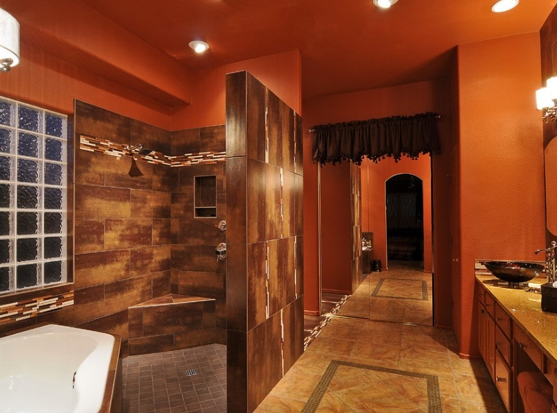 Large primary bathroom boasting a walk-in shower and a corner soaking tub surrounded by stunning walls. The room also offers decorated flooring and a brown sink counter with vessel sinks.