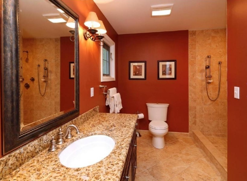 Primary bathroom with a gorgeous sink counter lighted by classy wall lights. The room also has an open shower with beige tiles floors and walls.