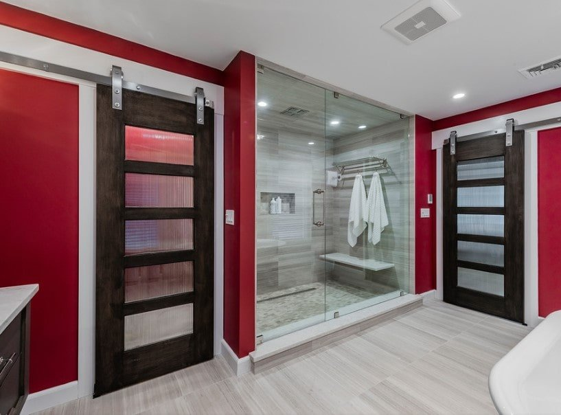 Primary bathroom featuring red walls and light gray hardwood floors. The room offers a walk-in shower room and a freestanding tub.