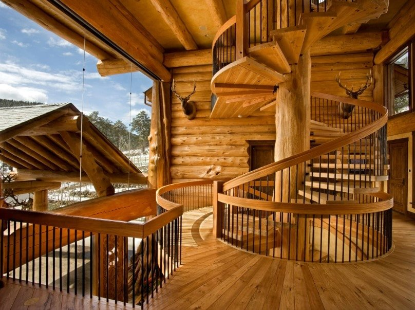 A large rustic house boasting a spiral staircase with hardwood steps, hardwood handrails and iron railings. The home features logs walls and hardwood floors.