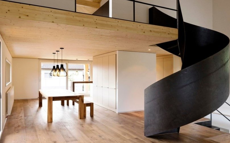 A modern house with a wooden ceiling and hardwood floors, together with a stunning black spiral staircase.