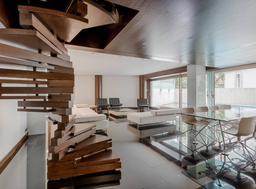 A contemporary home featuring a living space with modern furniture set along with a stunning dining table set. The home's staircase looks absolutely breathtaking.