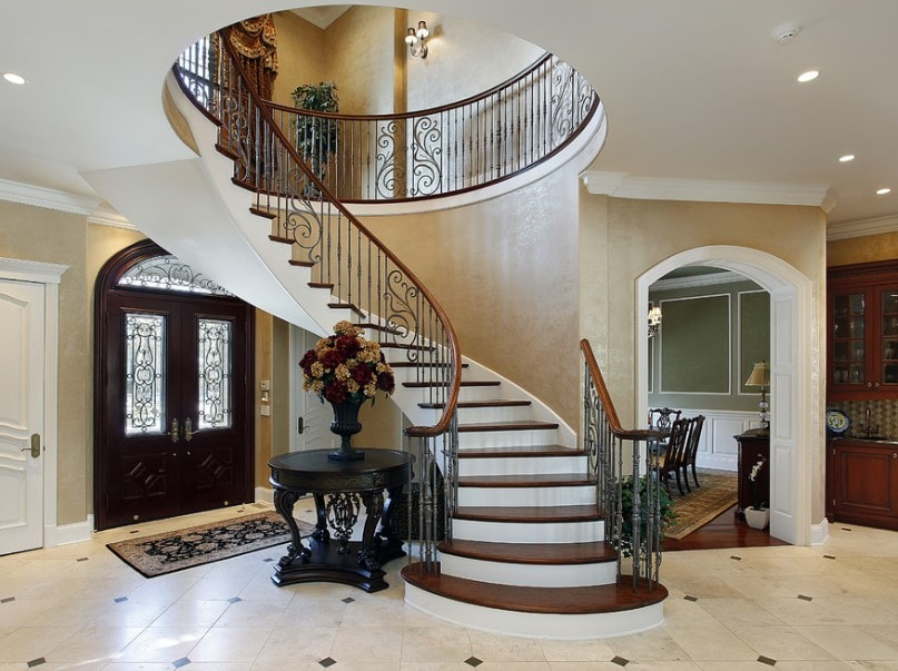 A home's foyer boasting an elegant staircase, along with classy tiles flooring and beige walls.