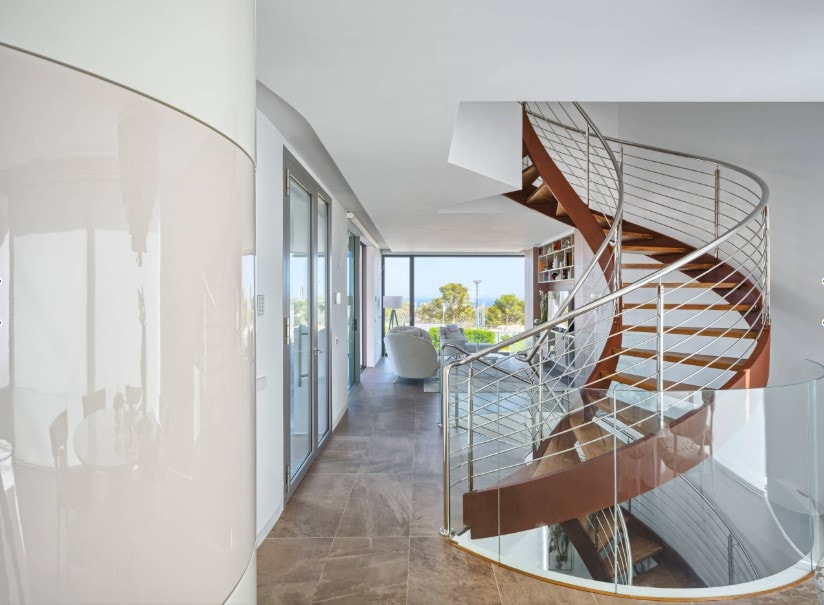 A view of the home's spiral staircase with hardwood steps and steel railings on the home's second floor. The home features tiles flooring and white walls and ceiling.