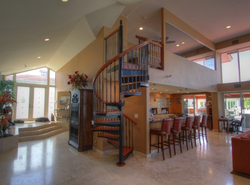 This home's foyer leads straight to the great room featuring a two-storey ceiling. It has a spiral staircase with hardwood steps leading to the home's second floor.