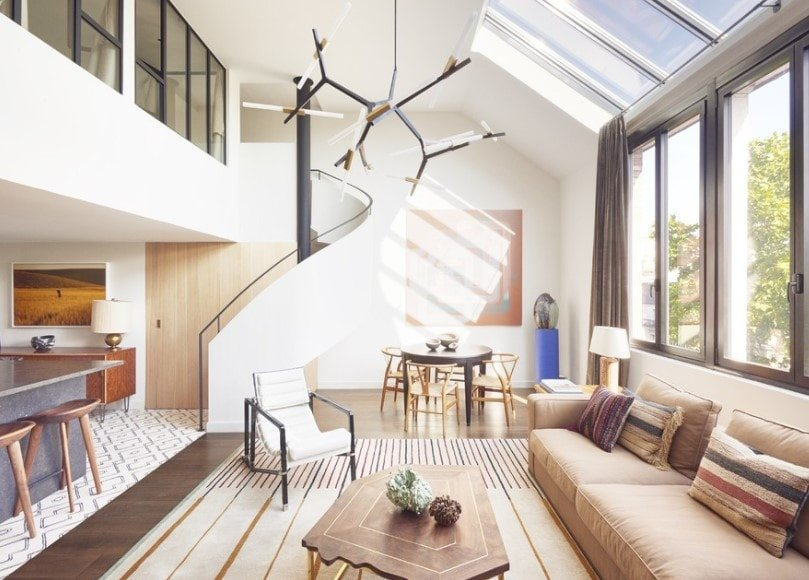 This home boasts a gorgeous spiral staircase with white railings and has a shed ceiling featuring skylights and a stylish ceiling light.