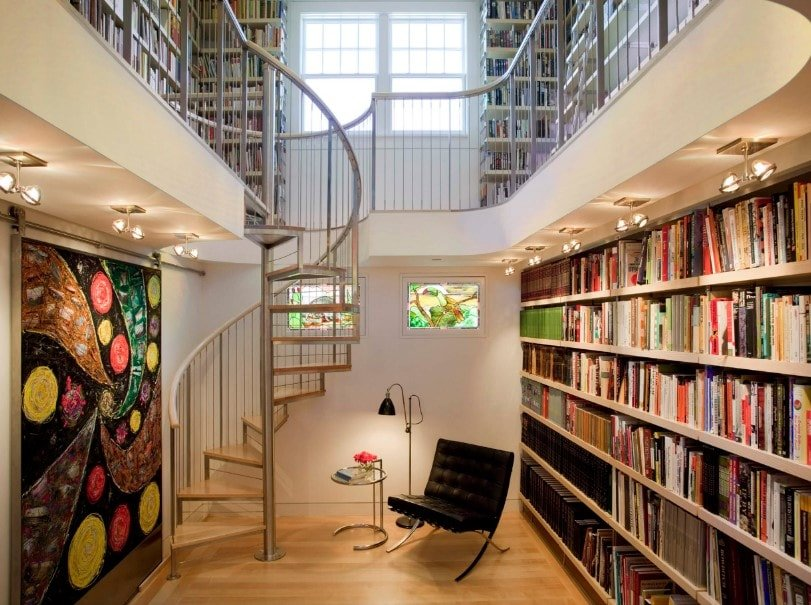 A two-storey library featuring multiple bookshelves and a spiral staircase leading to the library's second floor.