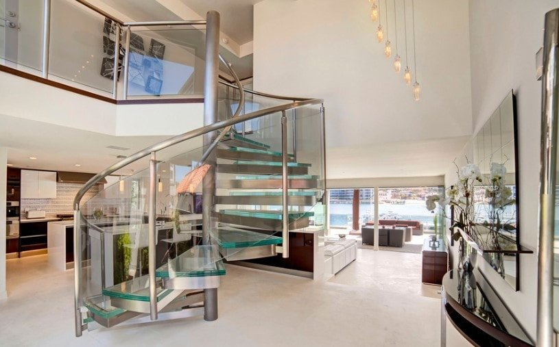 A focused shot at this modern home's stylish staircase boasting glass steps and glass railings, lighted by charming ceiling lights hanging from the high ceiling.